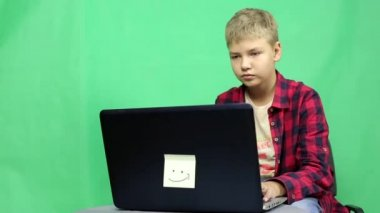 Teenager with a laptop on a green background.A young blond boy in a plaid shirt playing computer games while sitting at the computer.