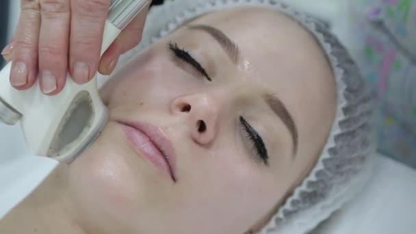 Odstraňování vrásek na obličeji a krku s masáží. Krásná blondýna vyhladí vrásky v oblasti obličeje a krku pomocí Lpg masáž v salonu krásy