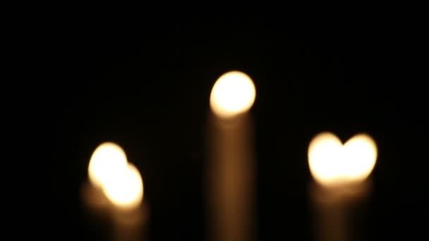 Pět hořících svíček ve svícnu. Skvrna, bez zaostření Svíčky v dřevěném svícnu hoří v noci na černém pozadí.
