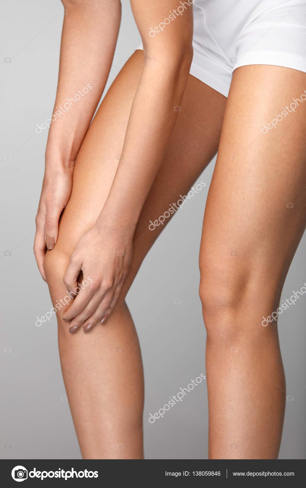 Rodilla dolorosa. Primer plano de mujer sentir dolor en las rodillas ...