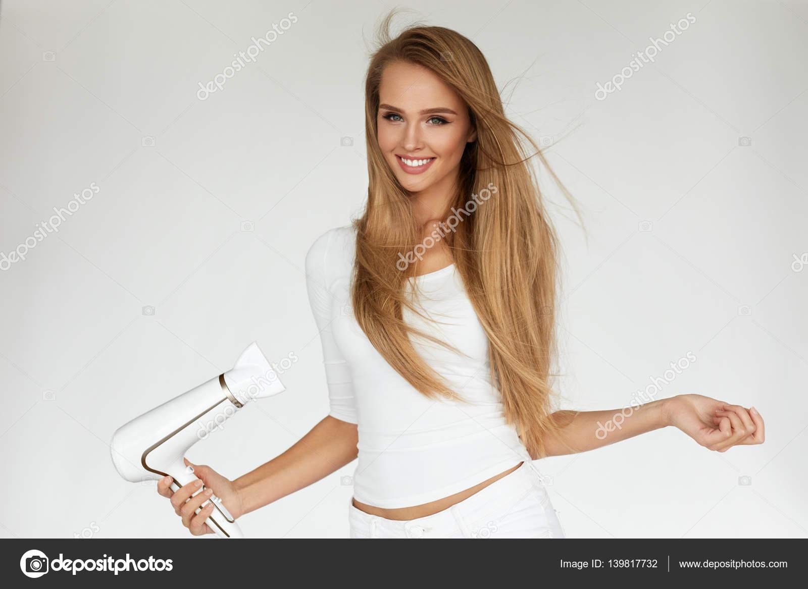 Haar trockner frau die schöne blonde lange glatte haare trocknen