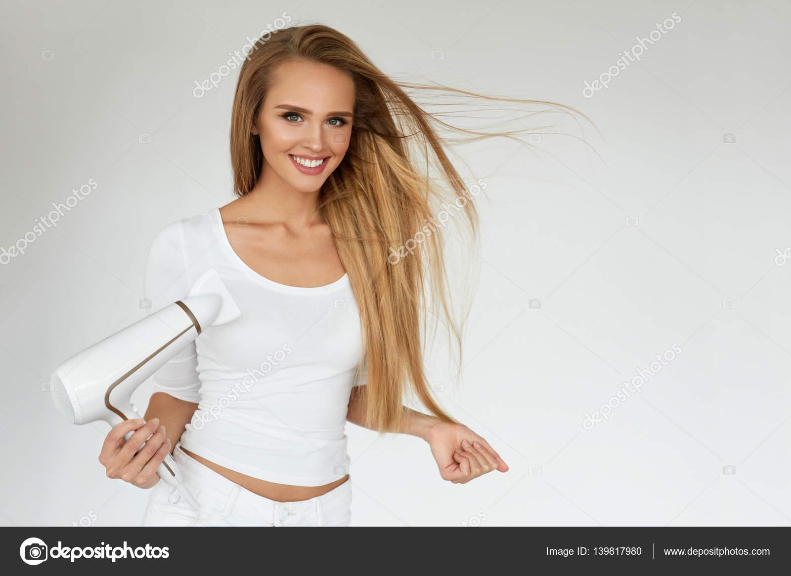 Hair care frau schöne lange blonde haare mit trockner trocknen
