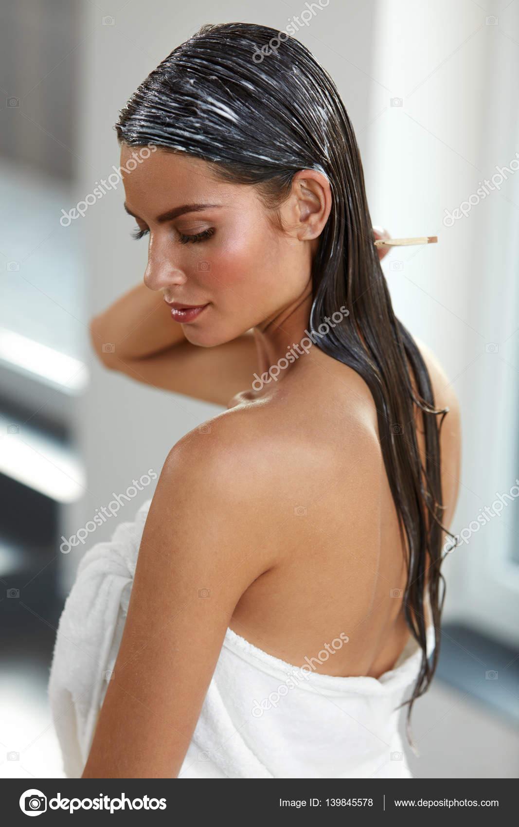 Bella donna che mette la maschera sui capelli bagnati ...