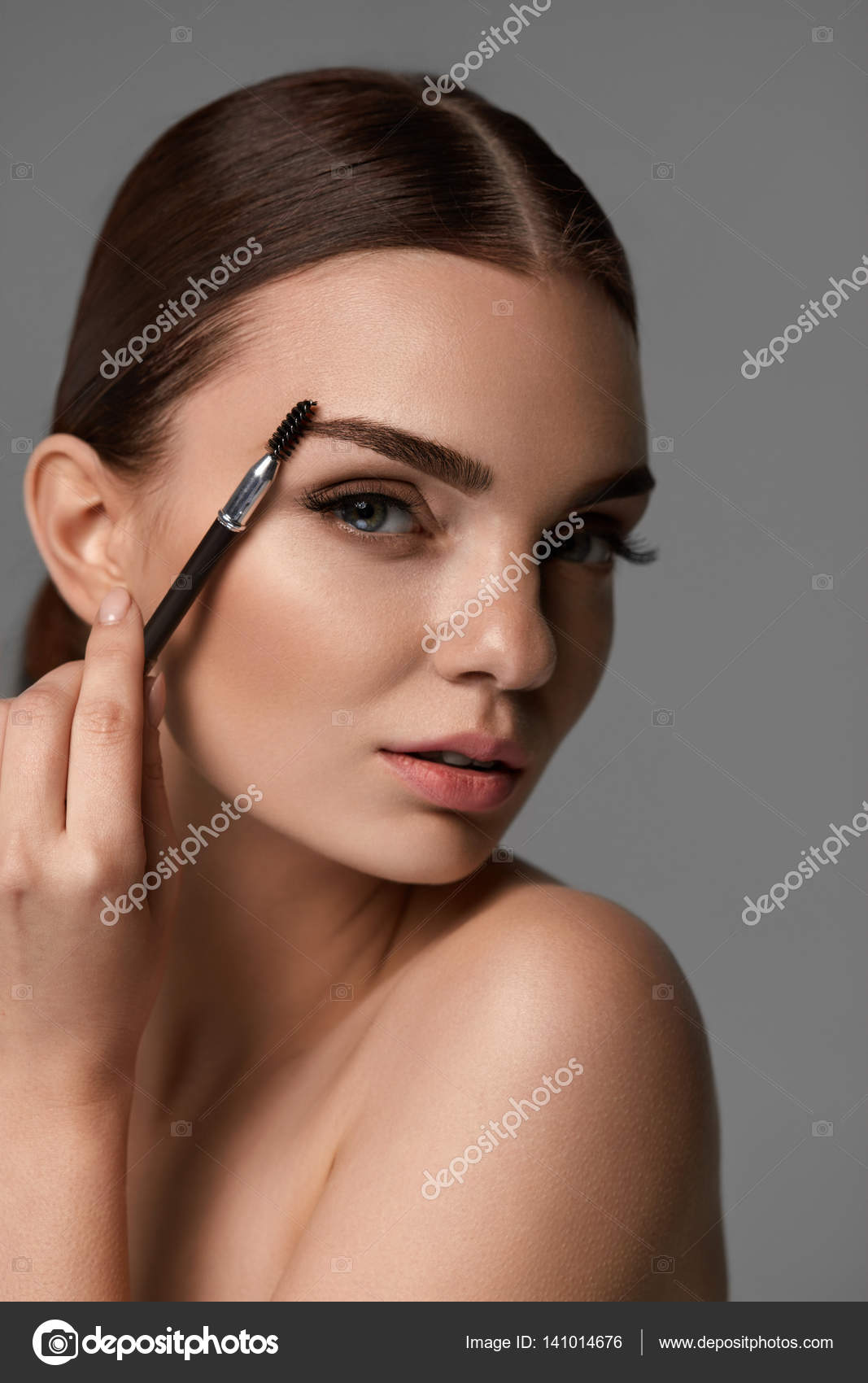 Beautiful Woman Brushing Eyebrows With Brow Tool Stock Photo