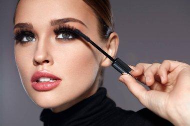 Beauty. Beautiful Woman Applying Black Mascara On Eyelashes