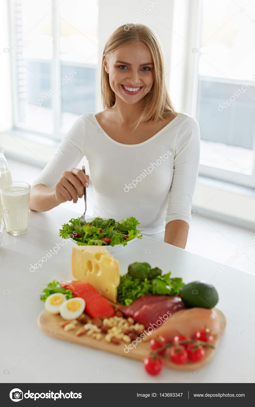 Gesunde Frau essen Salat In Küche, Lebensmittel auf Tisch ...