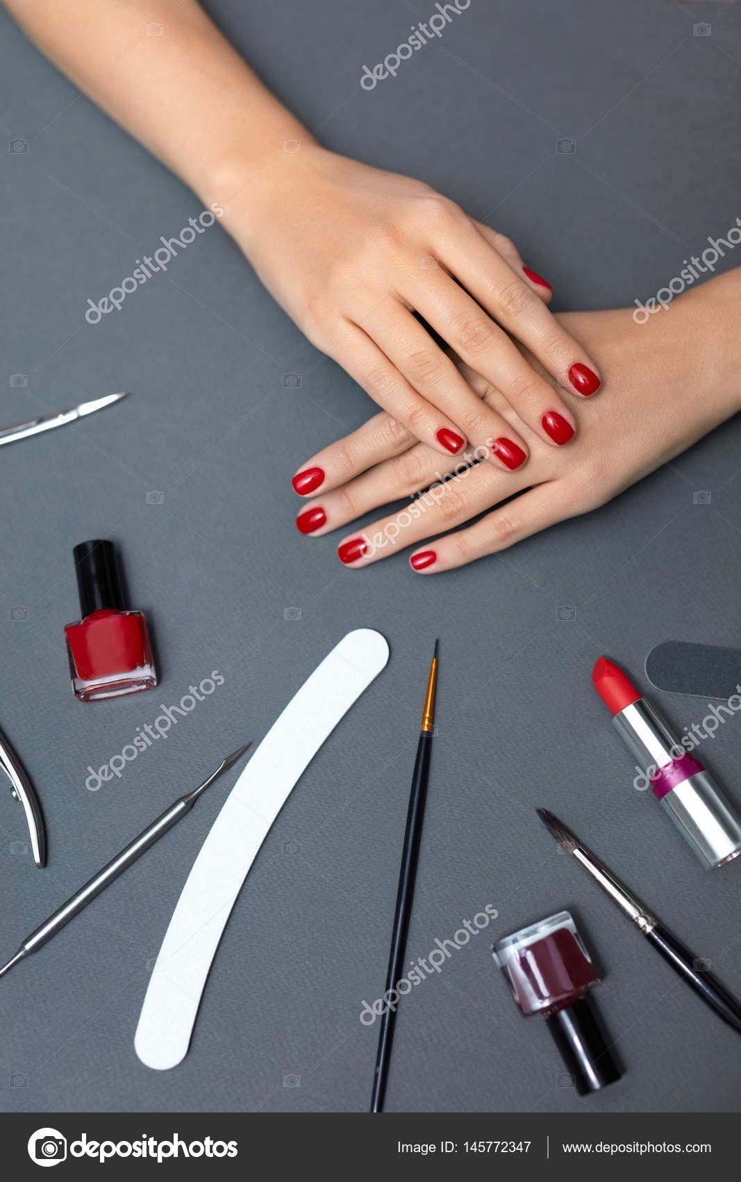 Belleza. Hermosa mujer uñas con esmalte de uñas rojo y herramientas ...
