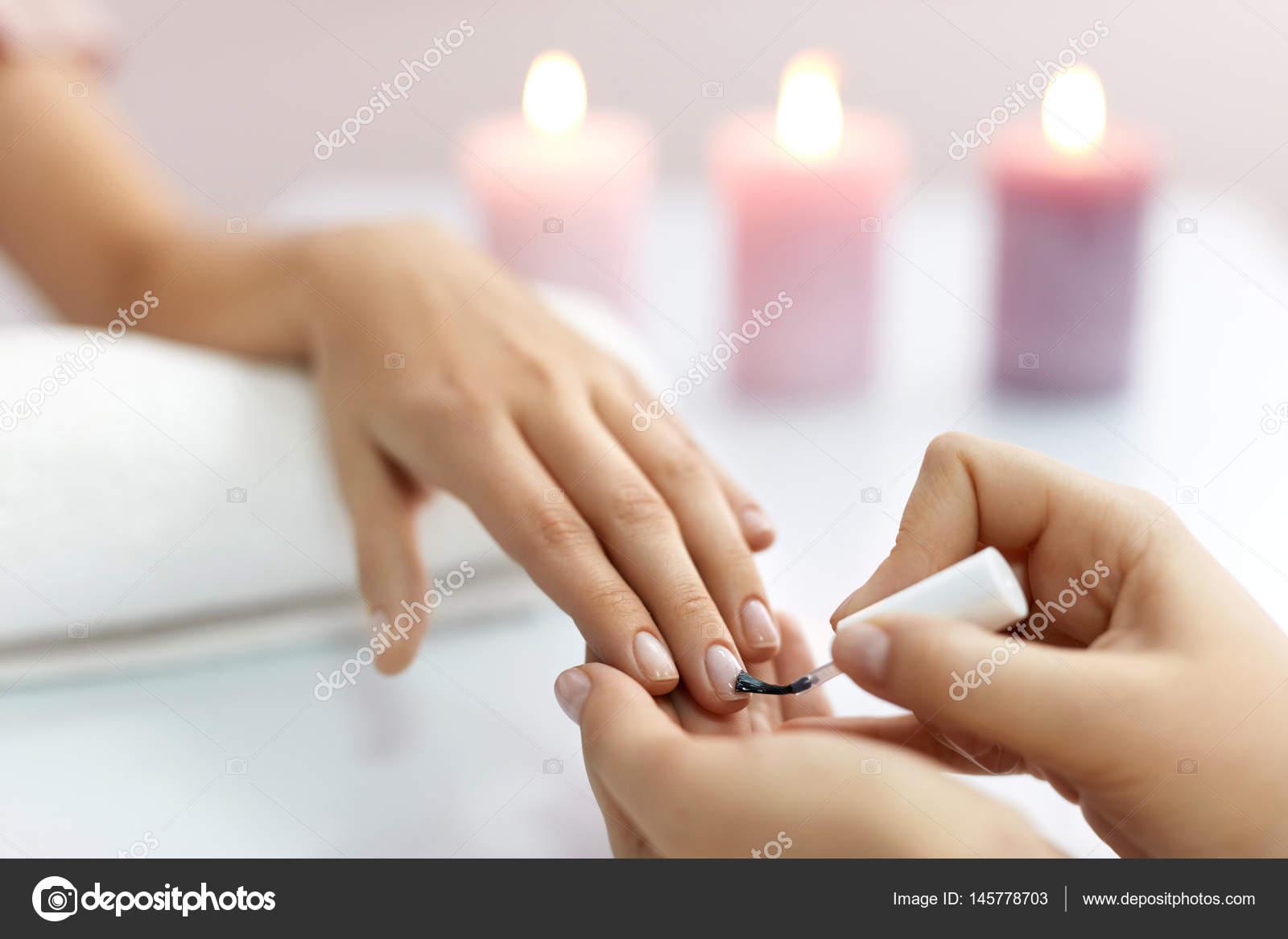 Cuidado de las uñas. Hermosa mujer manos aplicar esmalte en uñas ...