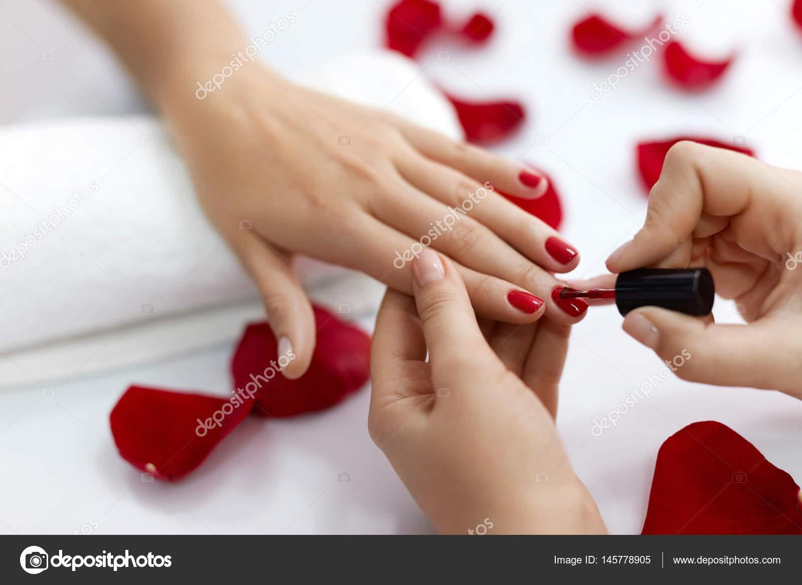 Woman Hands Polishing Nails With Red Nail Polish Stock Photo
