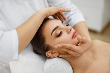 Woman Skin Care. Beautiful Female Model Receiving Face Massage