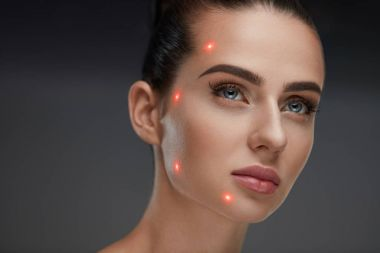 Closeup Of Beautiful Woman Face With Laser Points On Facial Skin