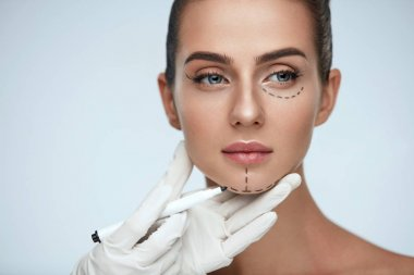 Treatment. Beautician Drawing Surgical Lines On Woman Face