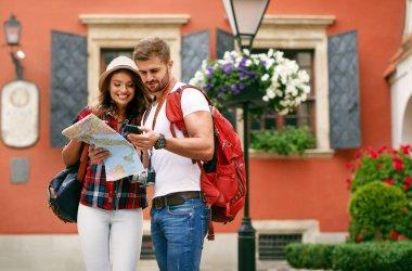 Beautiful Tourist Couple Traveling Using Map And Phone.