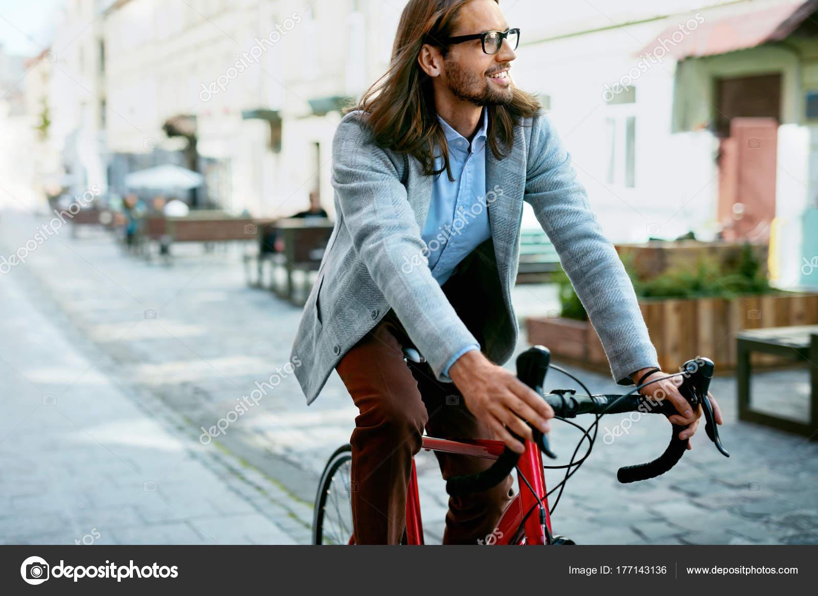 Κομψό αρσενικό ποδηλασία σε ποδήλατο στον δρόμο. Πορτραίτο του όμορφος  νεαρός χαμογελαστός άνθρωπος σε μοντέρνα Αντρικά ρούχα ιππασίας ποδήλατό σε  ... 44b94a31362