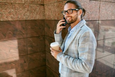 Man Talking On Phone Drinking Coffee Outdoors.