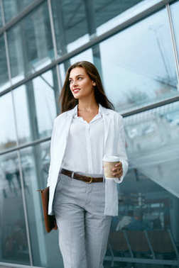 Beautiful Woman Walking With Cup Of Coffee Near Office Building.