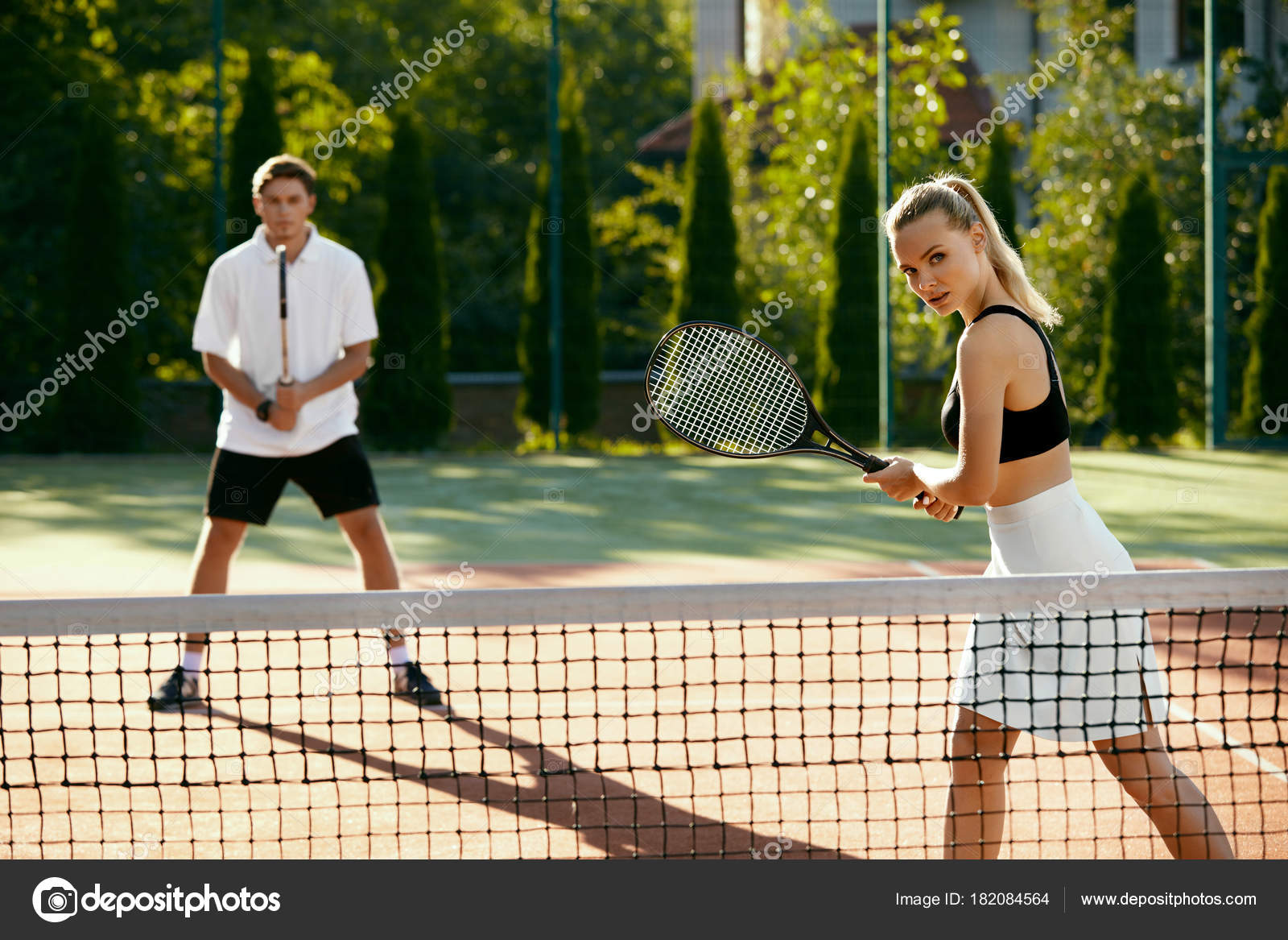 Man And Woman Playing Tennis On Court Stock Photo C Puhhha 182084564