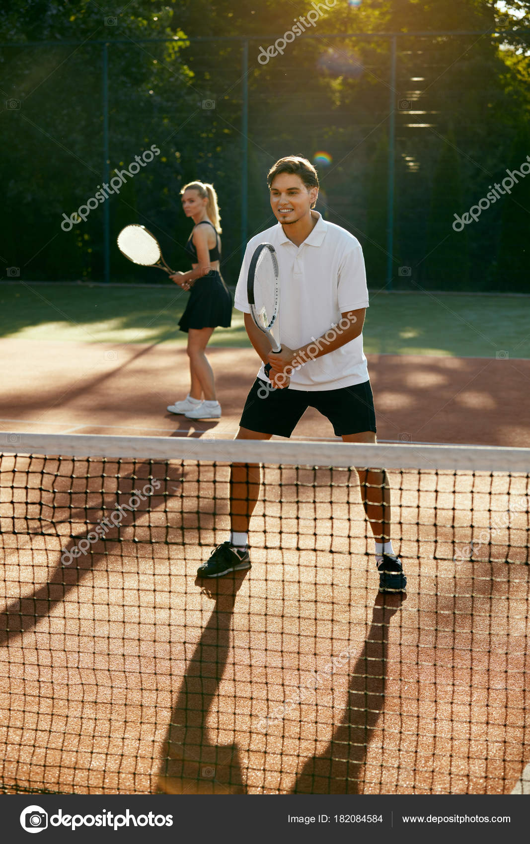 Man And Woman Playing Tennis On Court Stock Photo C Puhhha 182084584