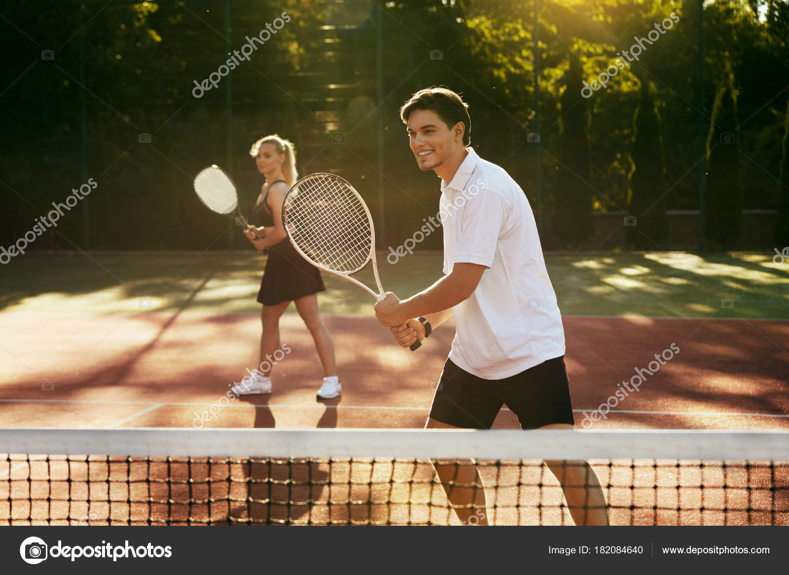 Man And Woman Playing Tennis On Court Stock Photo C Puhhha 182084640