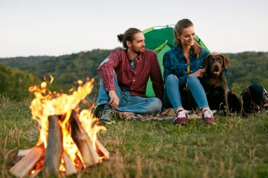 Man And Woman Traveling With Dog At Camp