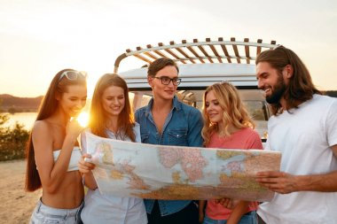 Summer Travel. Friends Using Map Near Car In Nature. Happy Smiling People Traveling In Bus On Weekend Vacation. Beautiful Young Men And Women Holding Map, Exploring Location On Trip. High Quality stock vector