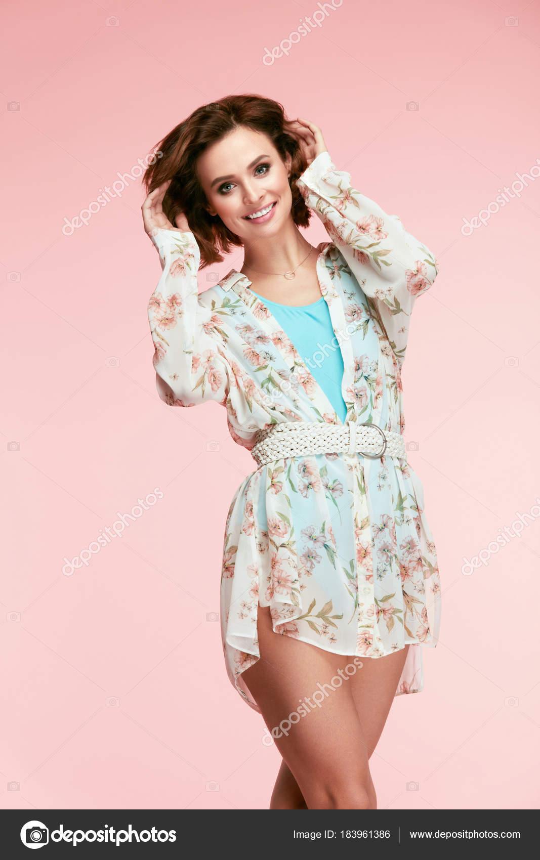 Bella mujer sonriente en ropa de moda primavera con pelo corto y Natural  belleza maquillaje en la cara. Retrato de niña feliz en vestido de flores  sobre ... d8c9a0d3a1b