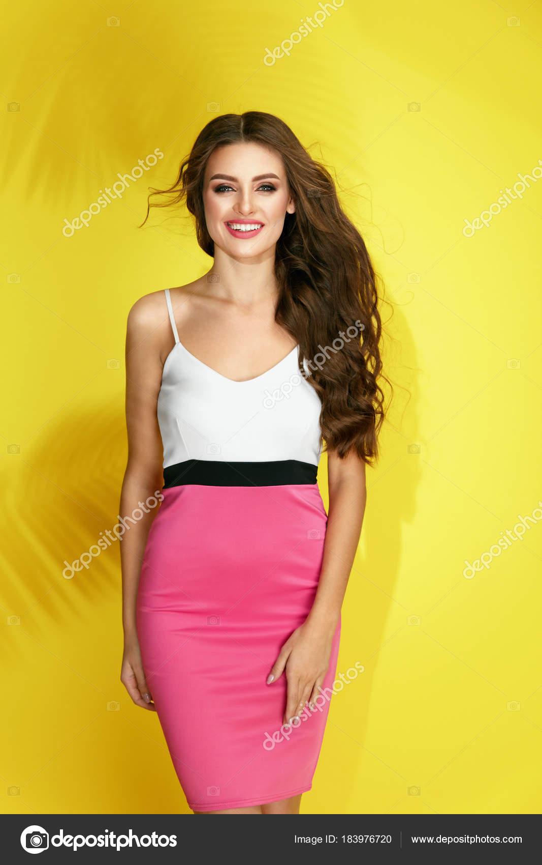 958de30d91 Divat-stílus. Divatos nyári ruha nő. Szép stílusos lány szexi színes  rózsaszín ruhában, hosszú göndör haj és a szépség és a smink sárga háttéren.