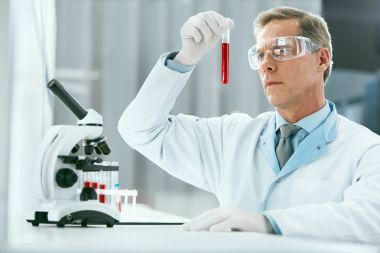 Laboratory Test. Male Doctor Analyzing Blood Sample. Portrait Of Handsome Mature Man Scientist Working With Test Tubes, Doing Research In Modern Medical Laboratory In Clinic. High Resolution. stock vector