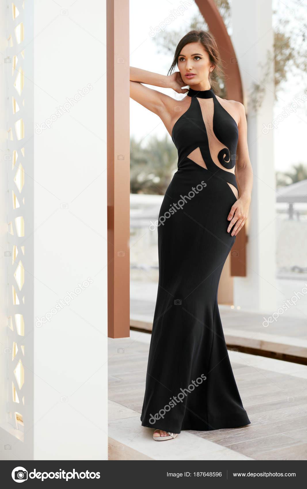 421c4449671b Moda ragazza In vestito nero lungo posa all aperto. Ritratto di bello  modello femminile alla moda In vestito da sera glamour con acconciatura  elegante posa ...