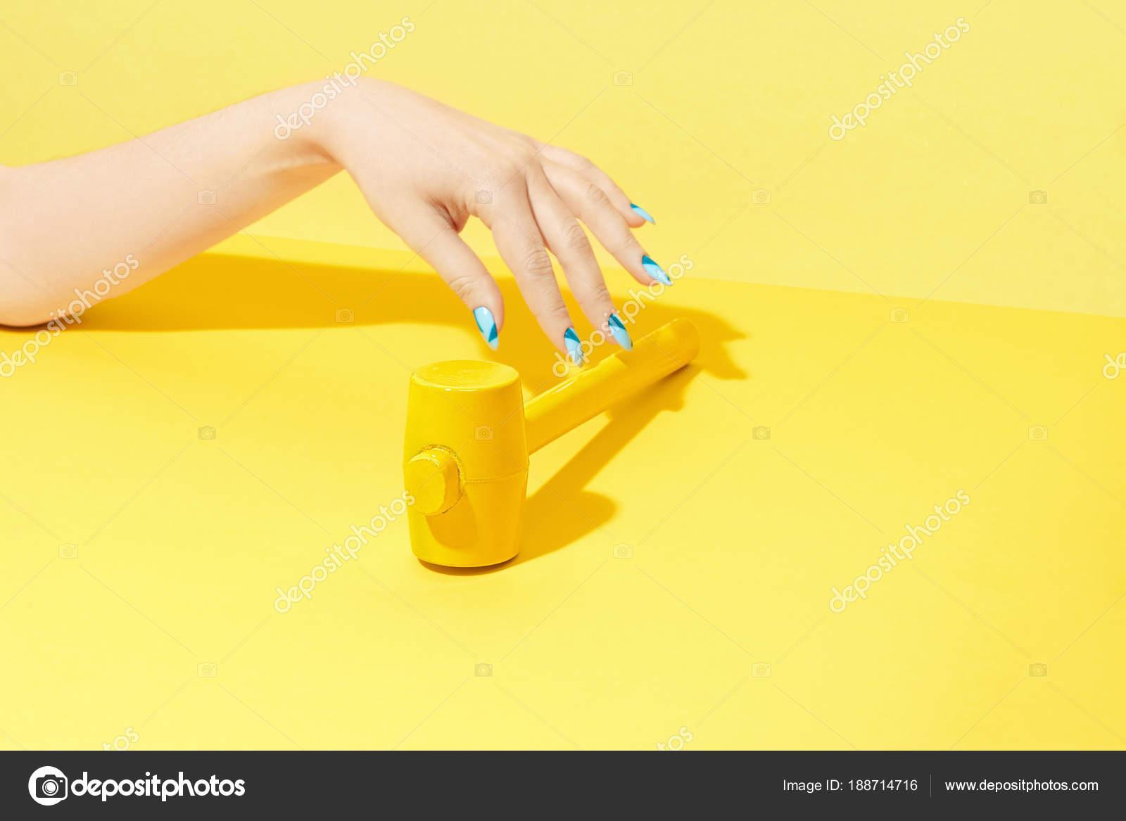 Design Nägel. Hand mit bunten Nägeln auf gelbem Hintergrund ...