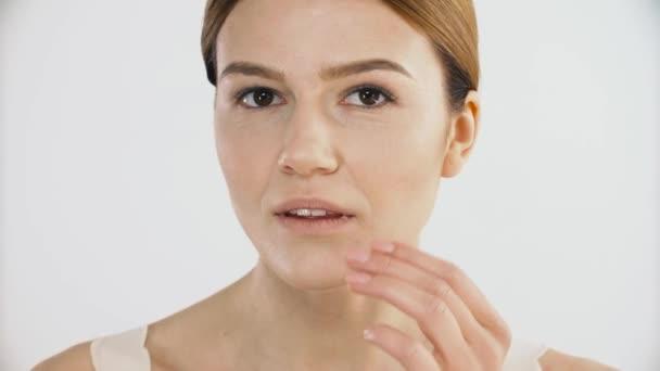 Péče o pleť. Zralé zdravé ženské Model dotýkání kůži obličeje s prsty. Detailní záběr na tvář krásná žena s čerstvou přírodní make-up dotýká čistým měkkým povrchem kůže. Pojetí krásy. Vysoké rozlišení