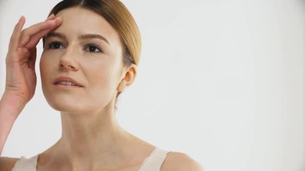 Kosmetika. Portrét atraktivní Sexy modelka hladí zdravou pleť. Closeup krásná zralá žena dotýká krása obličeje a úsměvu. Kosmetické koncept. Vysoké rozlišení