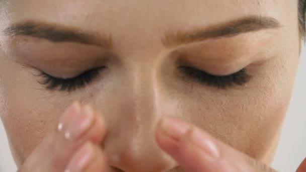 Péče o obličej. Closeup krásná žena s čerstvým make-up masírovat kůži pod očima. Zralý ženský Model s zdravou pokožku obličeje dotýká obličeje. Krása kosmetika. Vysoké rozlišení