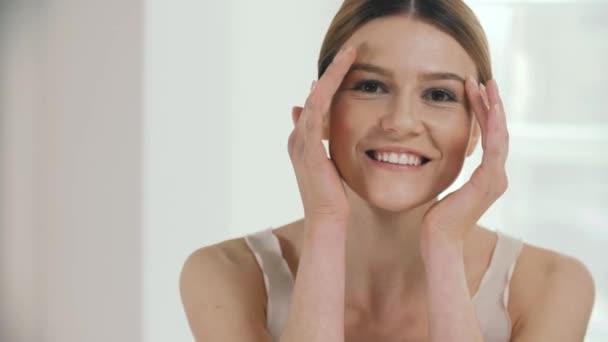 Női bőrápoló. Portré, szép mosolygó modell megérintette az arcát és kezét feje közelében. Vértes, boldog, érett nő, friss smink és egészséges bőr. Szépség fogalma. Nagy felbontású