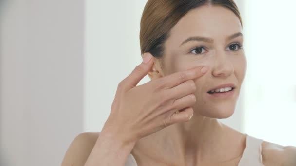 Krása. Detailní záběr na krásné ženské Model použití pásu kapaliny nadace na čerstvé kůži obličeje. Portrét zralá žena na tonální krém základnu na tvář. Kosmetické koncept. Vysoké rozlišení