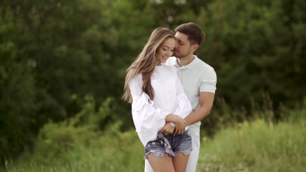 Nádherný pár v lásce všeobjímající v přírodě. Portrét šťastná žena a pohledný mladý muž v objímání a užívat si letní víkend. Lidé na romantické rande venku