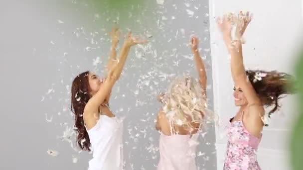 Gyönyörű lányok otthon Party, szórakozás. Boldog női barátok-divatos fehérneműk pizsamában, toll repülő, és élvezi a pizsama Party játék.