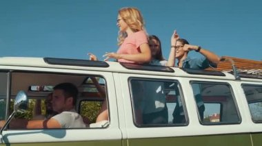Happy Friends Traveling By Car, Having Fun In Summer. Smiling Young Men And Beautiful Women Dancing And Laughing While Having Travel In Retro Bus With Open Car Roof.