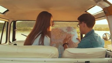 Friends Using Map Traveling In Car In Summer. Handsome Man In Glasses And Beautiful Smiling Woman Holding Map In Hands While Having Trip Outdoors. Young People Travel On Weekend