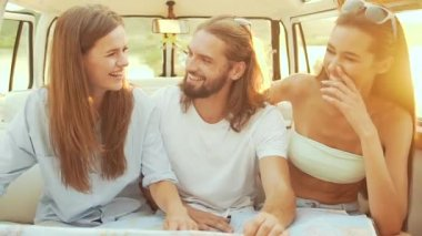 People Using Map Traveling In Summer. Smiling Happy Young Friends Using Map, Enjoying Weekend Trip On Sunny Day. Man And Women Having Fun In Car. Travel And Tourism.