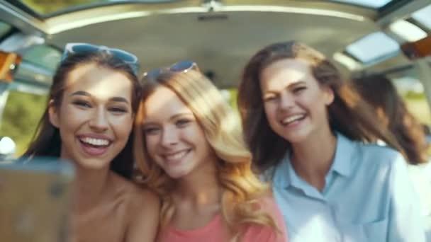 Happy přátelé baví v létě cestovat v autě, pomocí telefonu. Krásné usměvavé dívky fotografování na mobilním telefonu na slunečný letní den, letní cestování na dovolenou se těší.