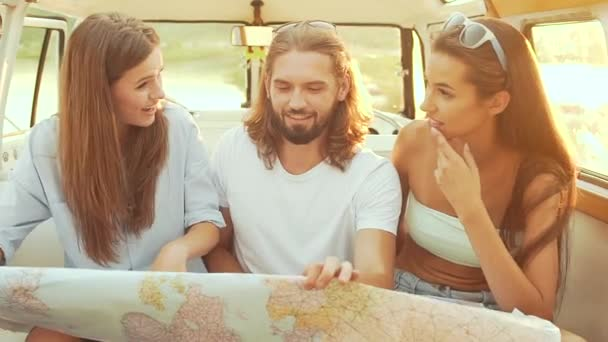 Lidí, kteří používají mapy na cestách v létě. Usmíval se šťastný mladí přátelé pomocí mapy, se těší víkendový výlet na slunečný den. Muži a ženy baví v autě. Cestování a cestovní ruch.