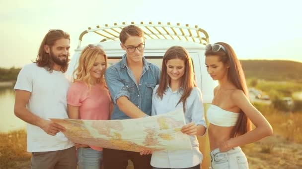 Young People With Map Near Car In Summer. Group Of Happy Smiling Friends Searching Destination Location On Map, Enjoying Travel To Nature On Vacation. Men And Women Traveling On Weekend