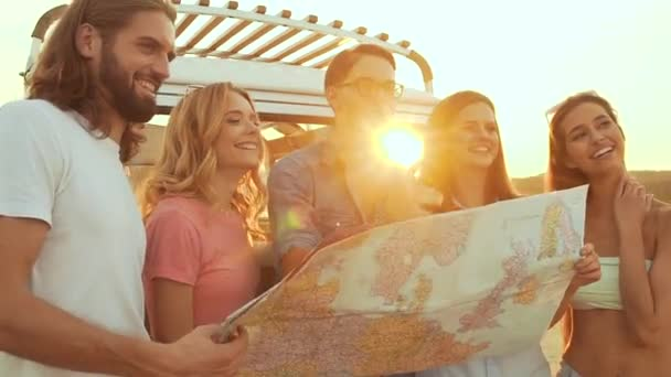 Summer Travel. Friends Using Map Near Car In Nature. Happy Smiling People Traveling In Bus On Weekend Vacation. Beautiful Young Men And Women Holding Map, Exploring Location On Trip.