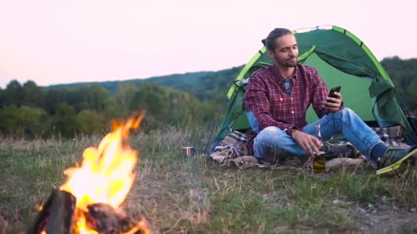 Ember utazik a természetben, tábor és mobiltelefon máglya közelében ült, és iszik sört.