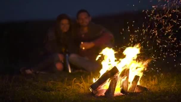 Romantisches Wochenende. Verliebtes Paar in der Nähe von Zelten und Lagerfeuer beim Umarmen und Ausruhen im Urlaub im Freien.