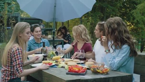 Menschen, die sich gesund ernähren, sitzen am Esstisch bei Grillparty im Freien