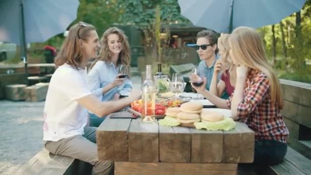 Gruppe von Freunden trinken Wein und Fotografieren am Telefon sitzen am Tisch auf Sommer-Wochenende In der Natur