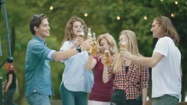 Freunde haben Spaß und trinken Bier, jubeln mit Getränken und genießen Outdoor-Party im Sommer.