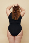 Plus Size Modell. Frau von hinten Porträt. Vollbusige Brünette im Rückenbody, die Hände auf dem Kopf und die Haare berühren. Positives Konzept auf beigem Hintergrund.